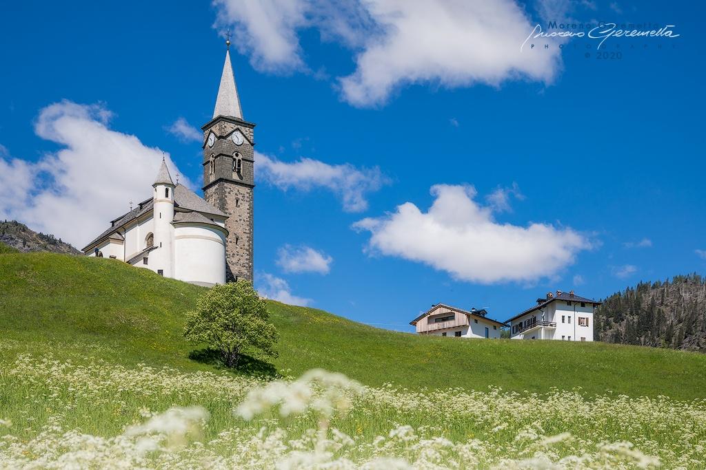 Chiesa di Laste dedicata a San Gottardo con i prati verdi a primavera - Agordino